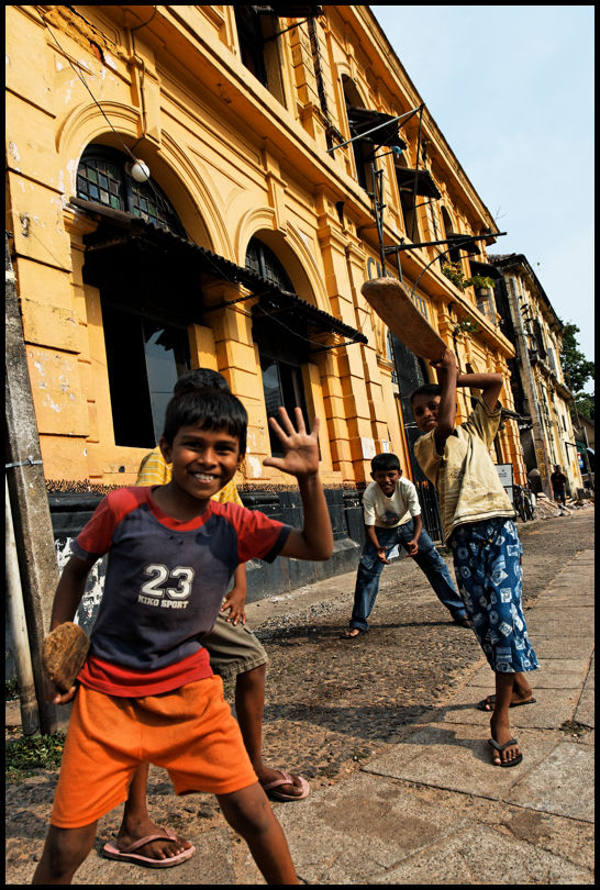 Children playing cricket in Colombo's streets.