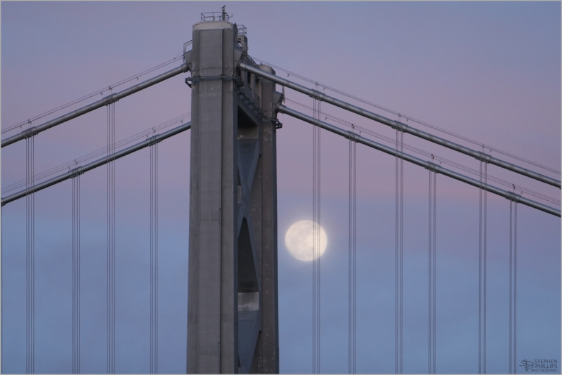 silver moon through cables of the Bay Bridge