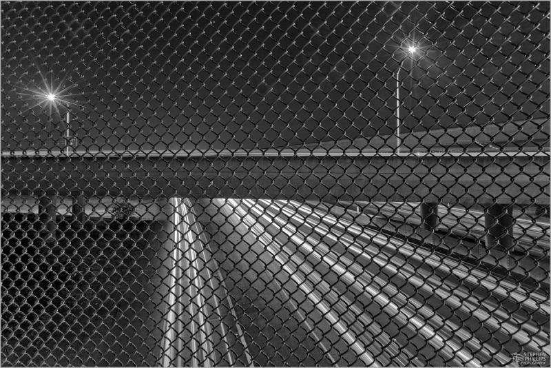 freeway lights through a fence