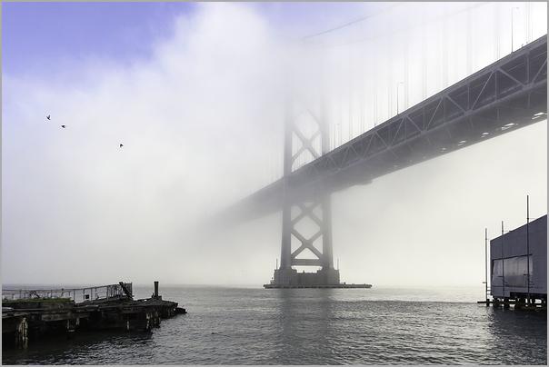 San Francisco Oakland Bay Bridge out of dense fog