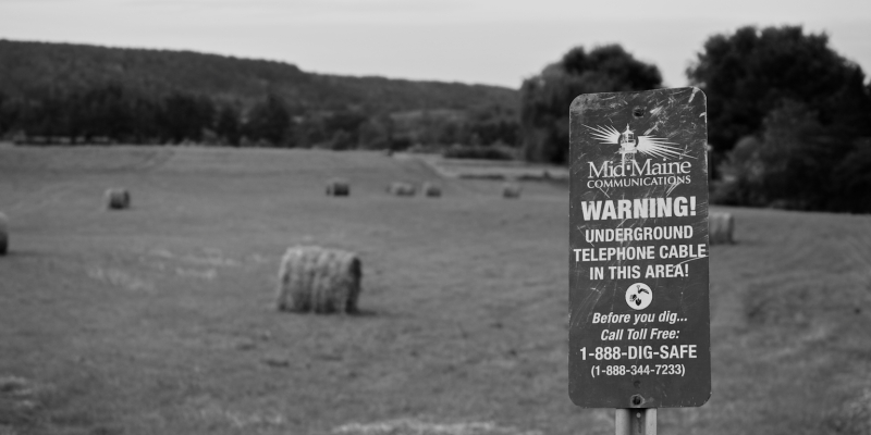A sign on the edge of a field.