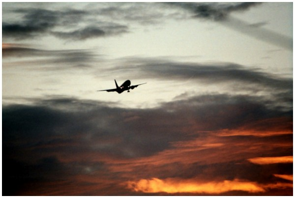 An airplane flying into the sunset