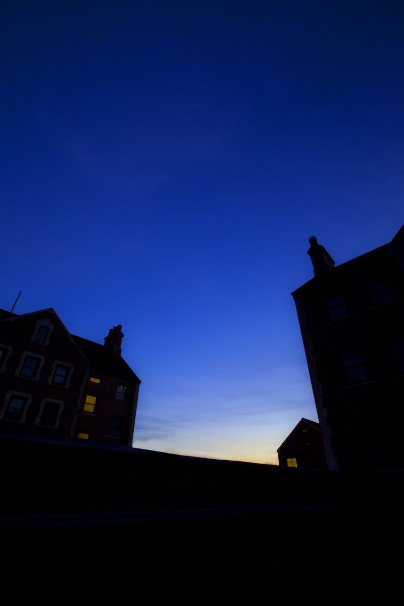 Silhouette of buildings against a blue sky gradien