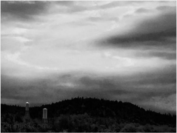 water towers hills landscape rural clouds dark sky