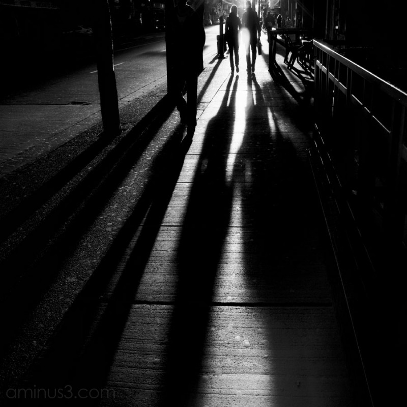 long shadows of people walking in black and white