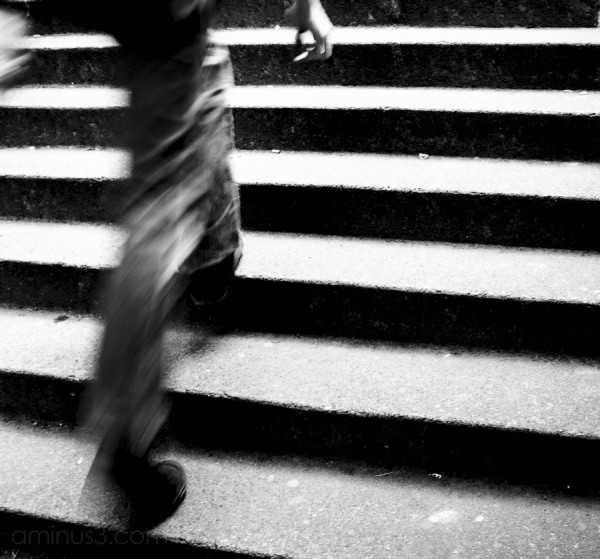 blurrred man walking up stairs holding cigarette