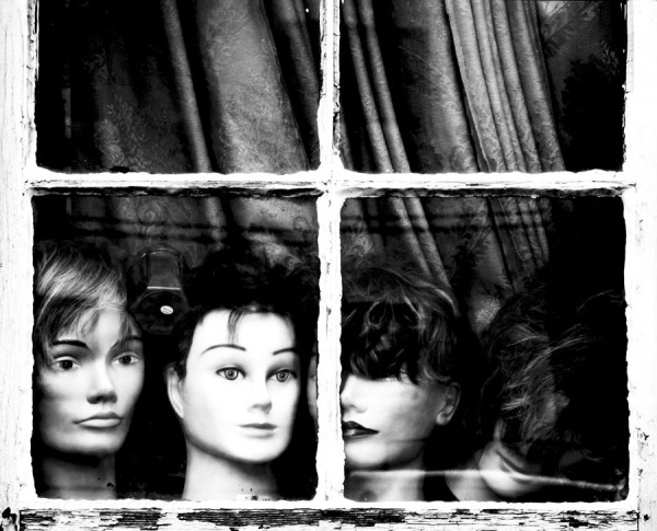 mannequin heads in the window of a house