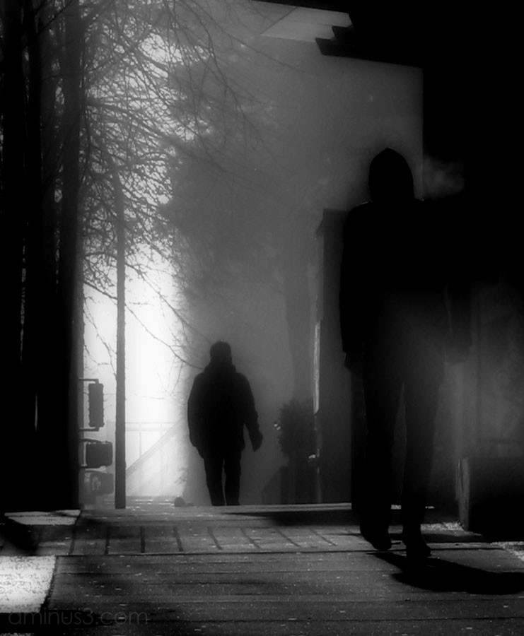 two men walking in fog on street