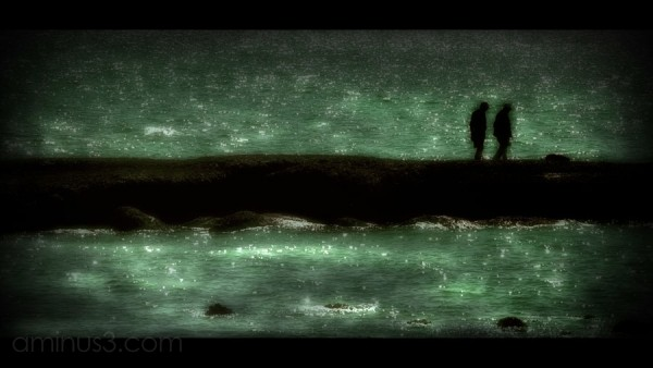 two people  along the jetty, green ocean