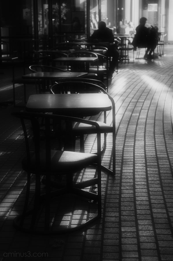 stream of light follows people at tables & chairs