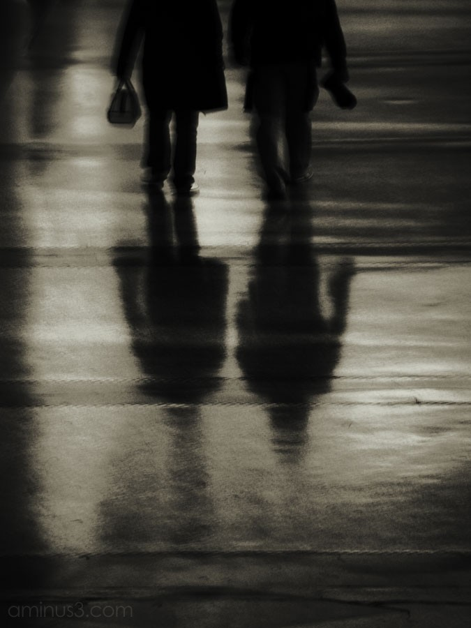 two people walking, their reflection on floor