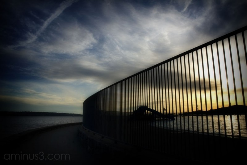 sunset against the ocean, slide and fence