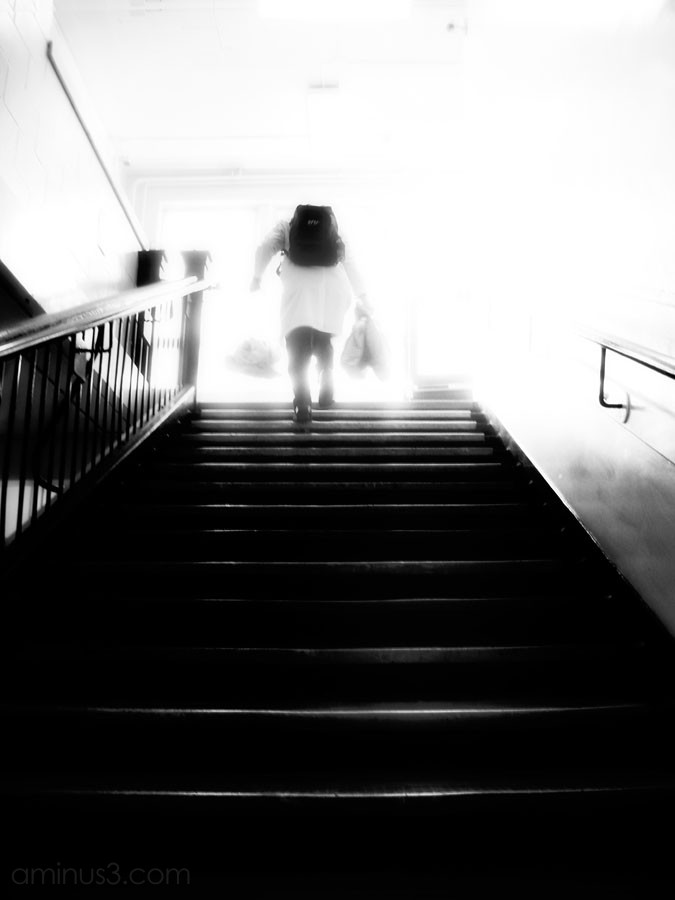 man walking up stairs into a white light