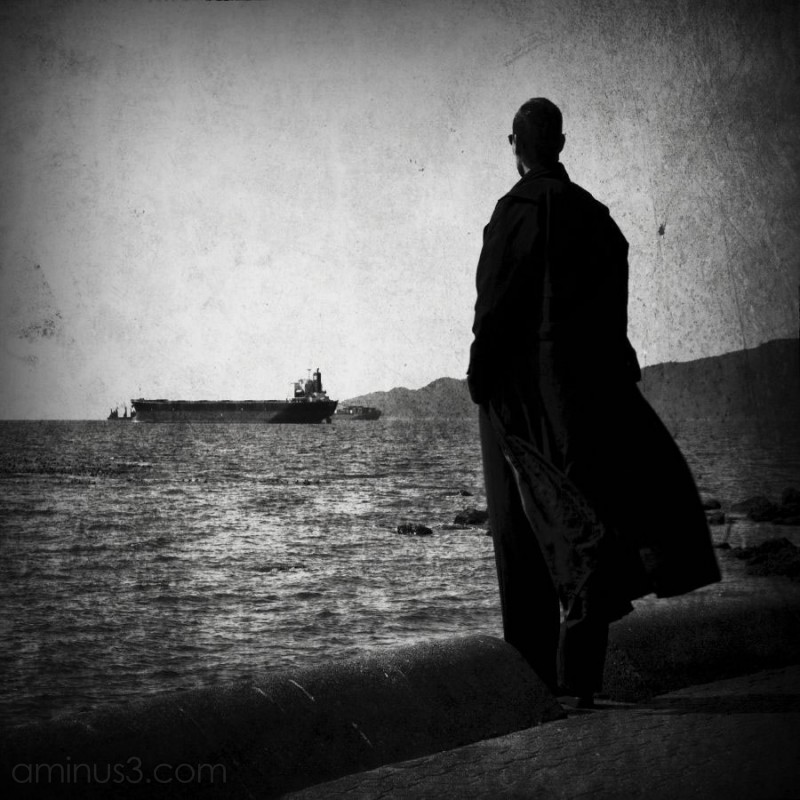 lone man staring off at a ship in the ocean