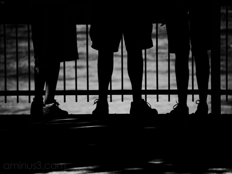 silhouette of legs of three men against iron fence