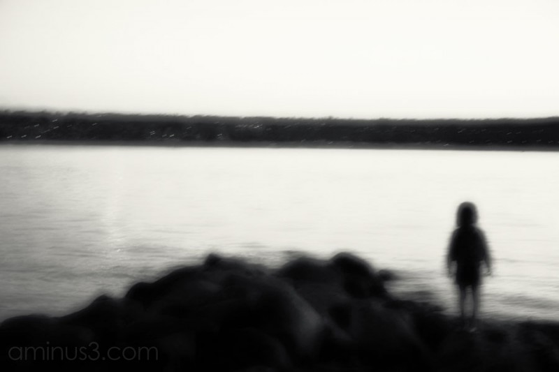 small blurred woman on beach looking for answers