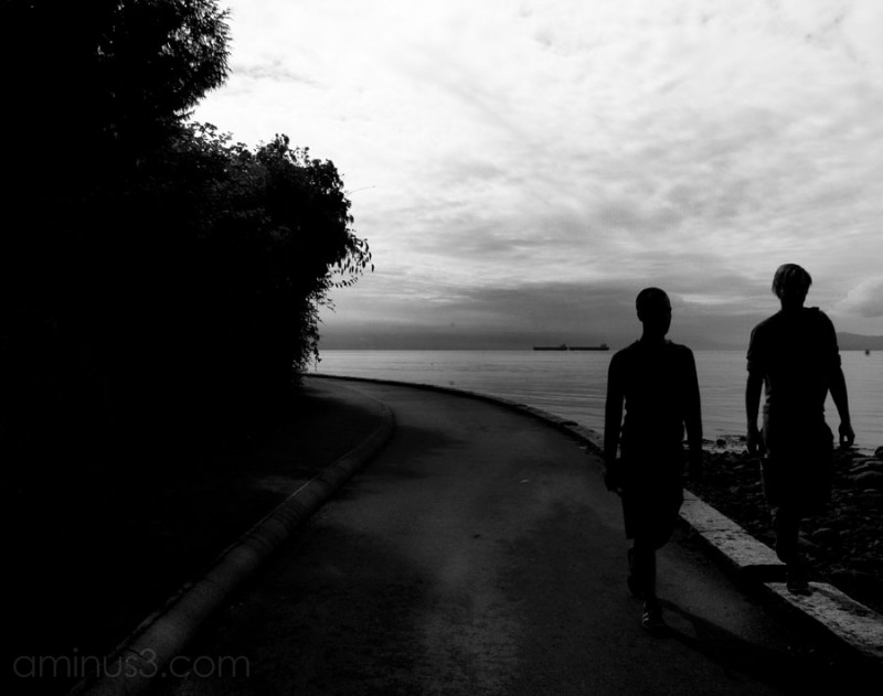 Two silhouetted people walking along a seawall