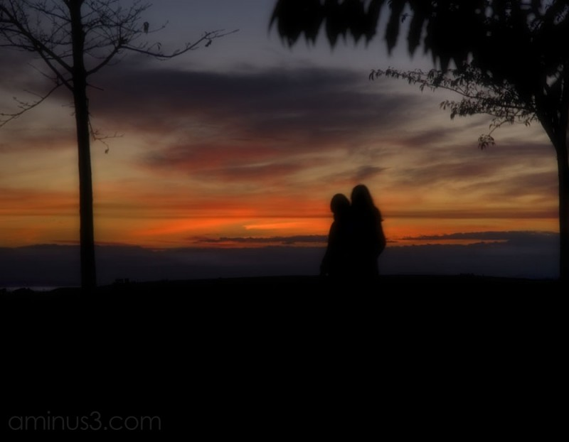 two silhouetted people walking in the sunset