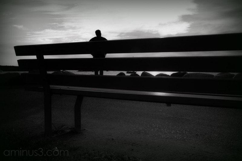 bench in foreground with man looking at ocean