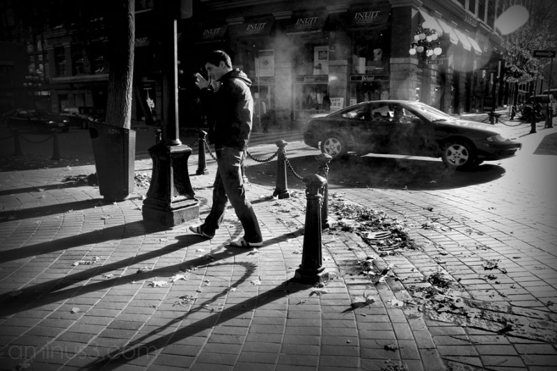 man crossing street, heavy shadows, steam