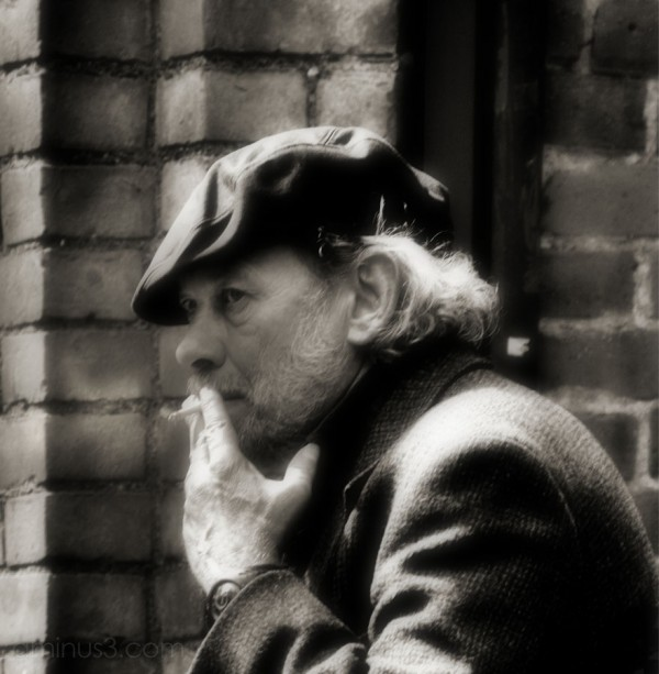 man smoking, against a brick wall