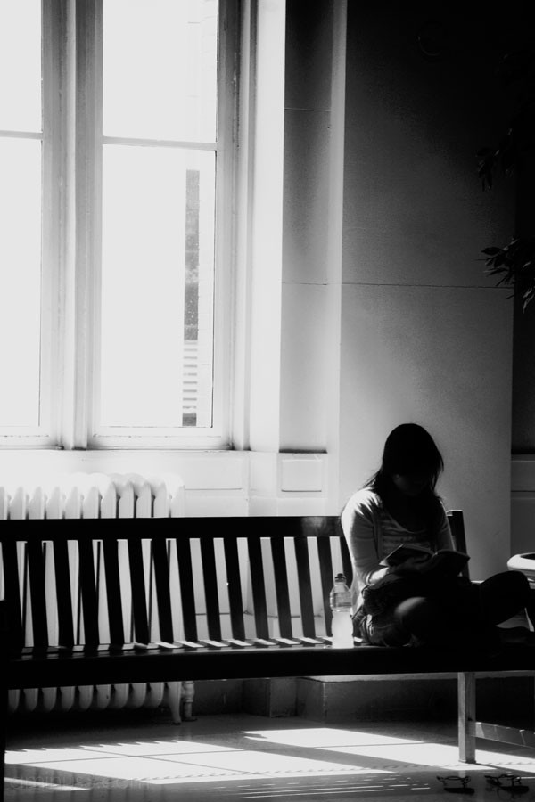 girl sitting on bench at train station, reading.