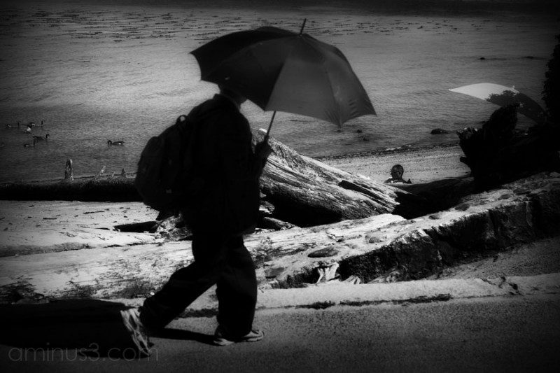 man skulking along a seawall holding umbrella