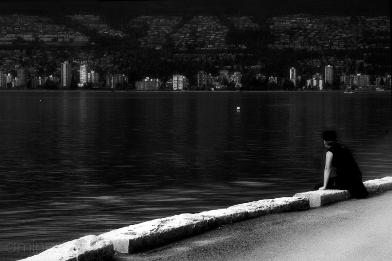 woman sitting on seawall staring at the city