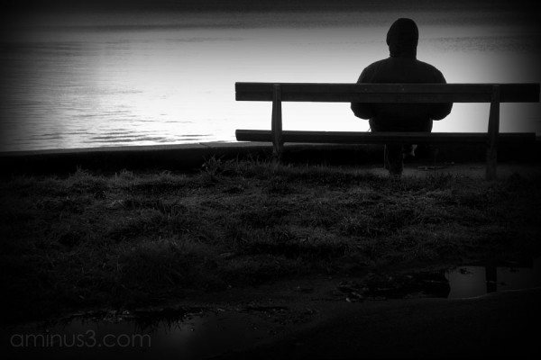 silhouette of a man on park bench staring at ocean