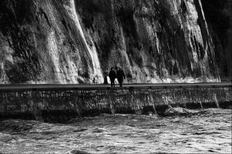 two people walking along a huge rock face