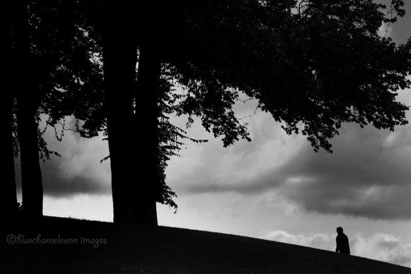 a lone man walking up a hill