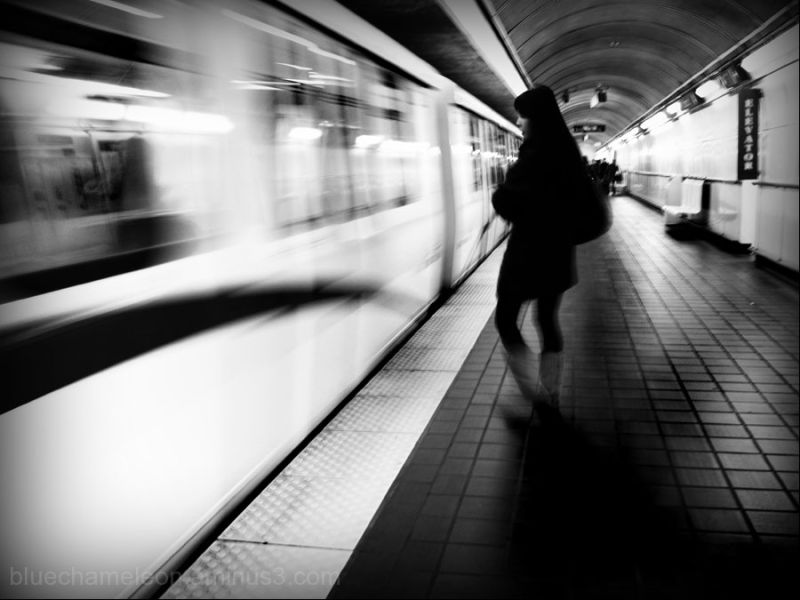 a woman waiting to get on a moving train