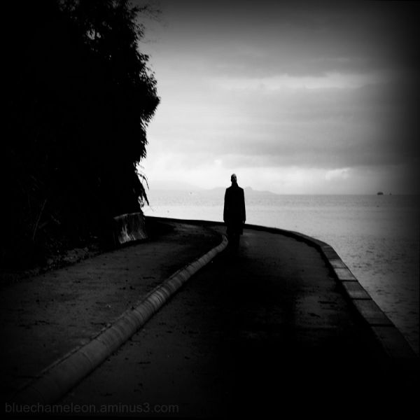 a lone tall man walking along a stormy seawall