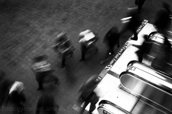 Looking down on blurred people leaving escalator