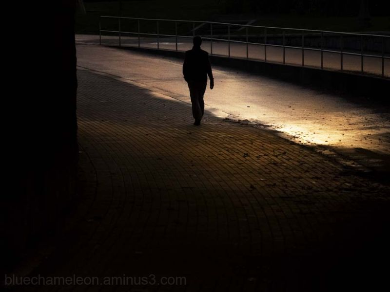 A man walking through a tunnel glowing gold