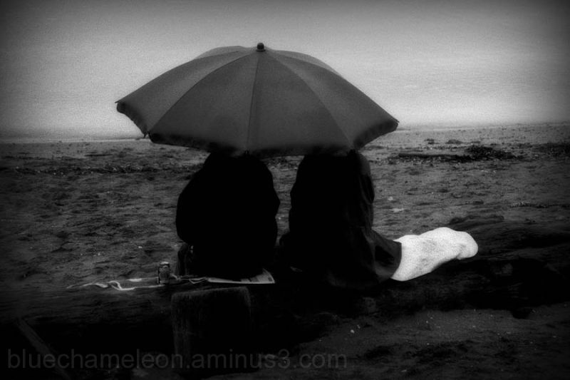 Two people sitting under umbrella at beach in rain