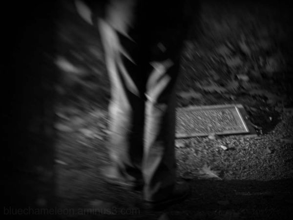 The legs of a man, blurred, standing by a memorial