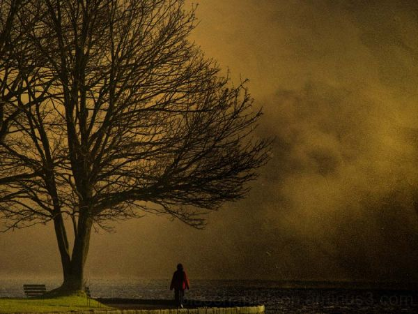 A lone man in red walking into a storm on seawall