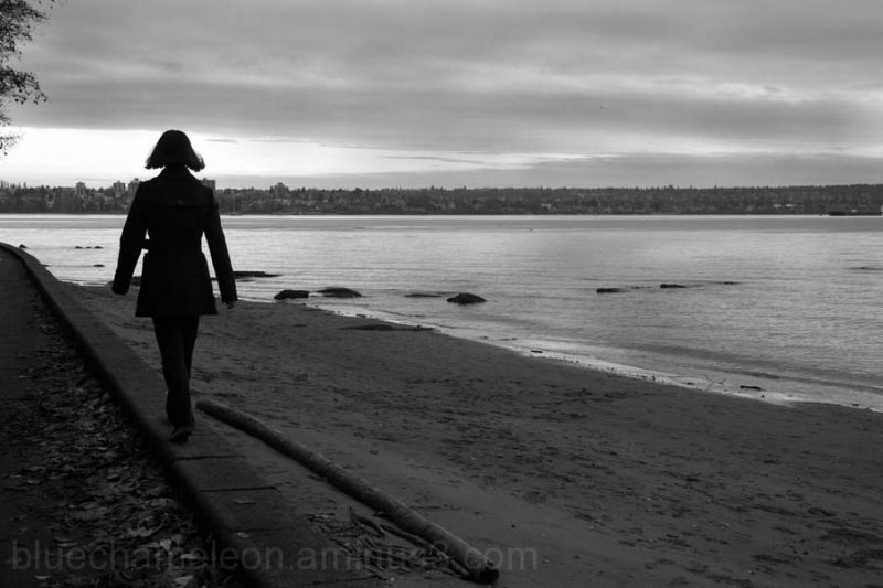 Silhouette of a woman walking along seawall