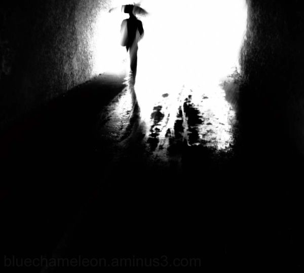 A silhouette man walking through tunnel in rain