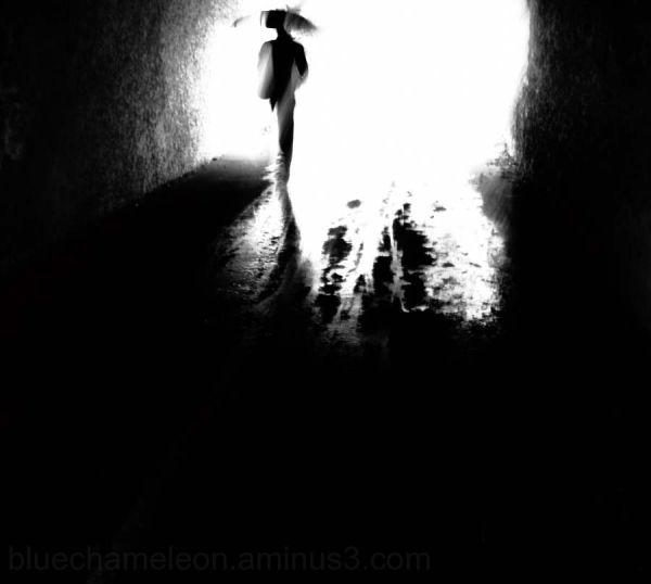 A silhouette man walking through tunnel in rain
