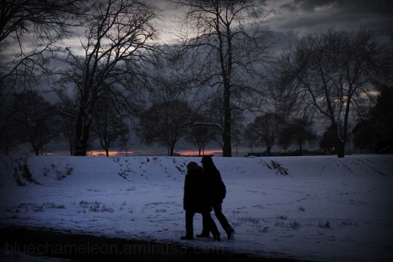 A silhouetted couple in snow at dusk