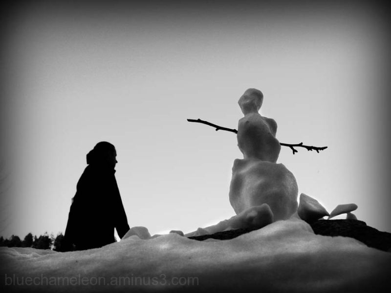 A snowman watching a woman walk by