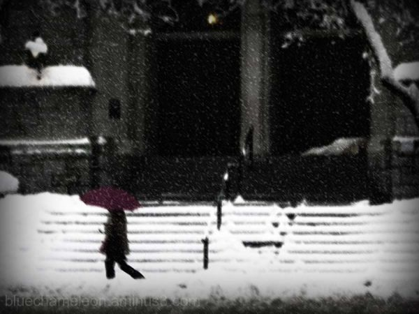 Woman walking by church steps in snow storm