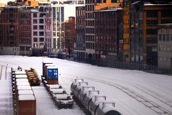 railway yard covered in snow, colour buildings