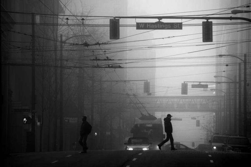2 people crossing the street in fog.