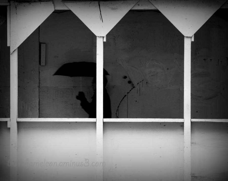 A man with umbrella walking under scaffolding