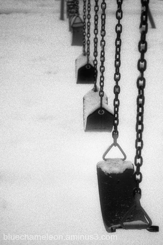 A set of swings, seats covered in snow