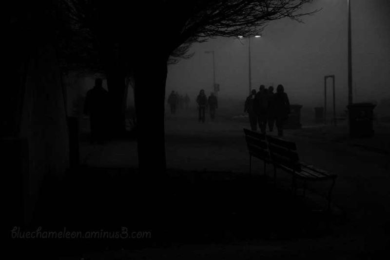 Groups of people walking on a dark foggy night