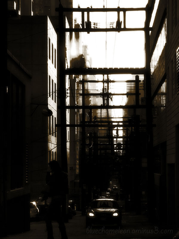 A silhouetted man crossing an alley in contrast